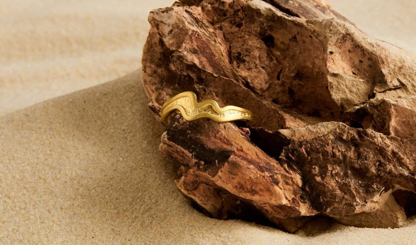 wavy gold ring set in a piece of petrified wood on light brown surface
