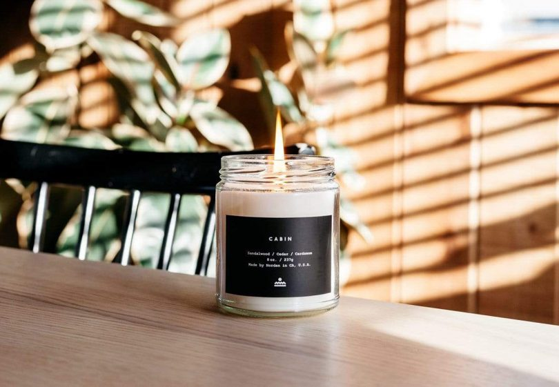 burning candle in glass jar with label in living space
