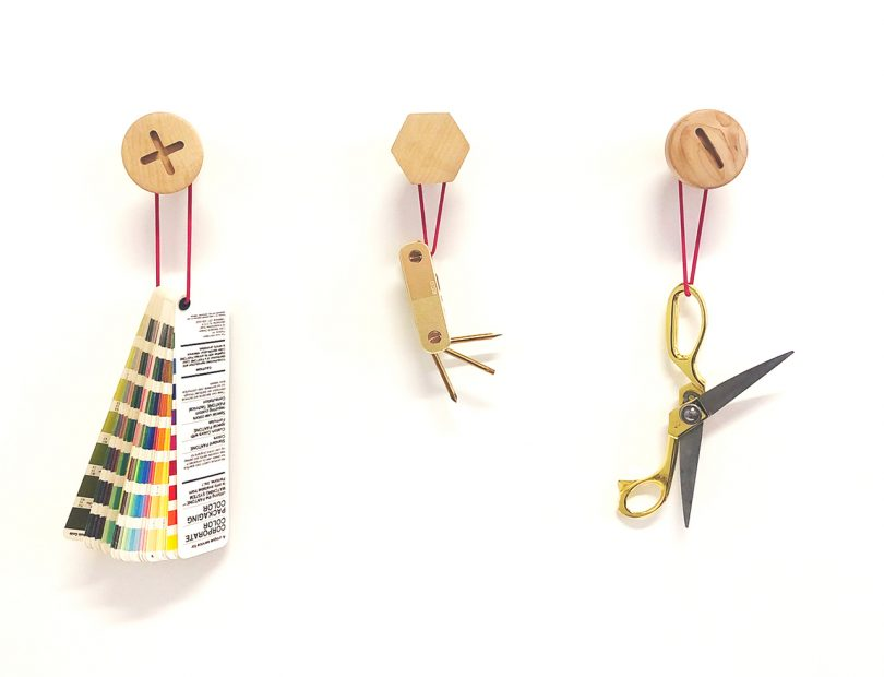 three wall hooks resembling screws with office supplies on white wall
