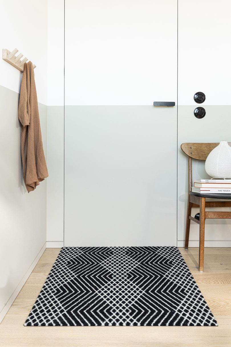black and white patterned door mat in front of grey and white entry door with chair to the right side