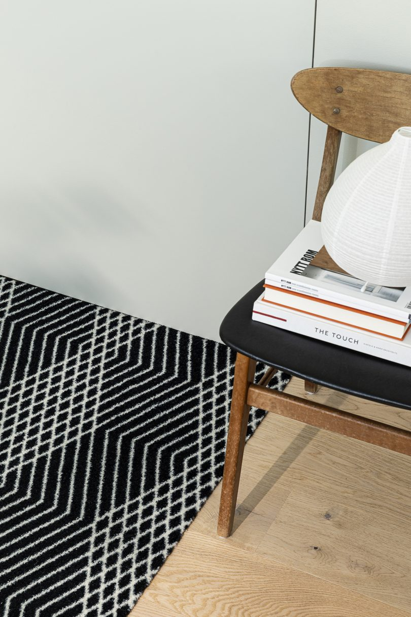 black and white patterned door mat detail with chair stacked with books on right