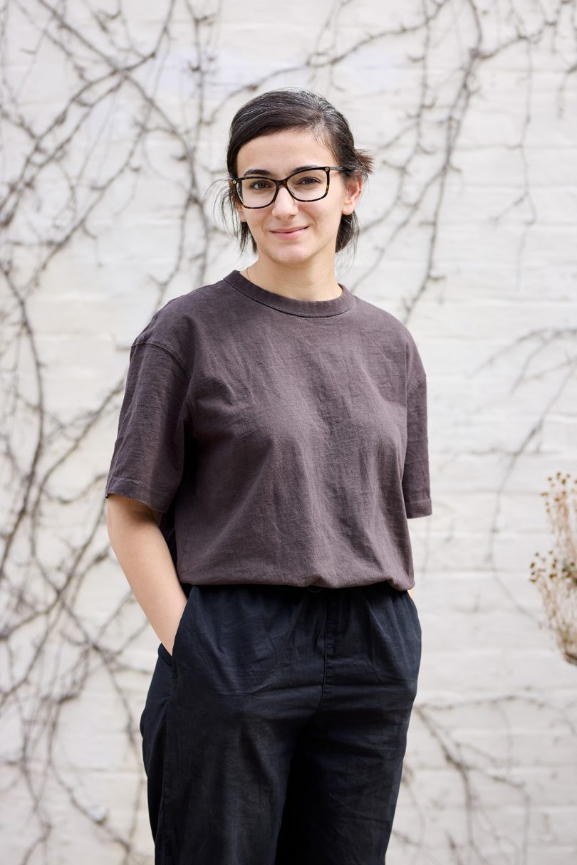 light skinned woman with dark hair wearing dark clothing and glasses