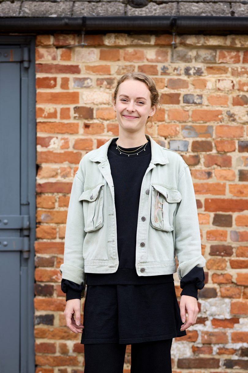 light skinned woman wearing black shirt and denim jacket standing in front of brick wall