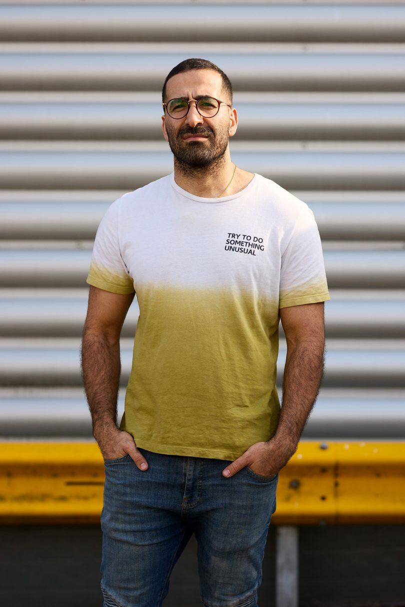 brown skinned man wearing yellow and white t-shirt, jeans, and glasses