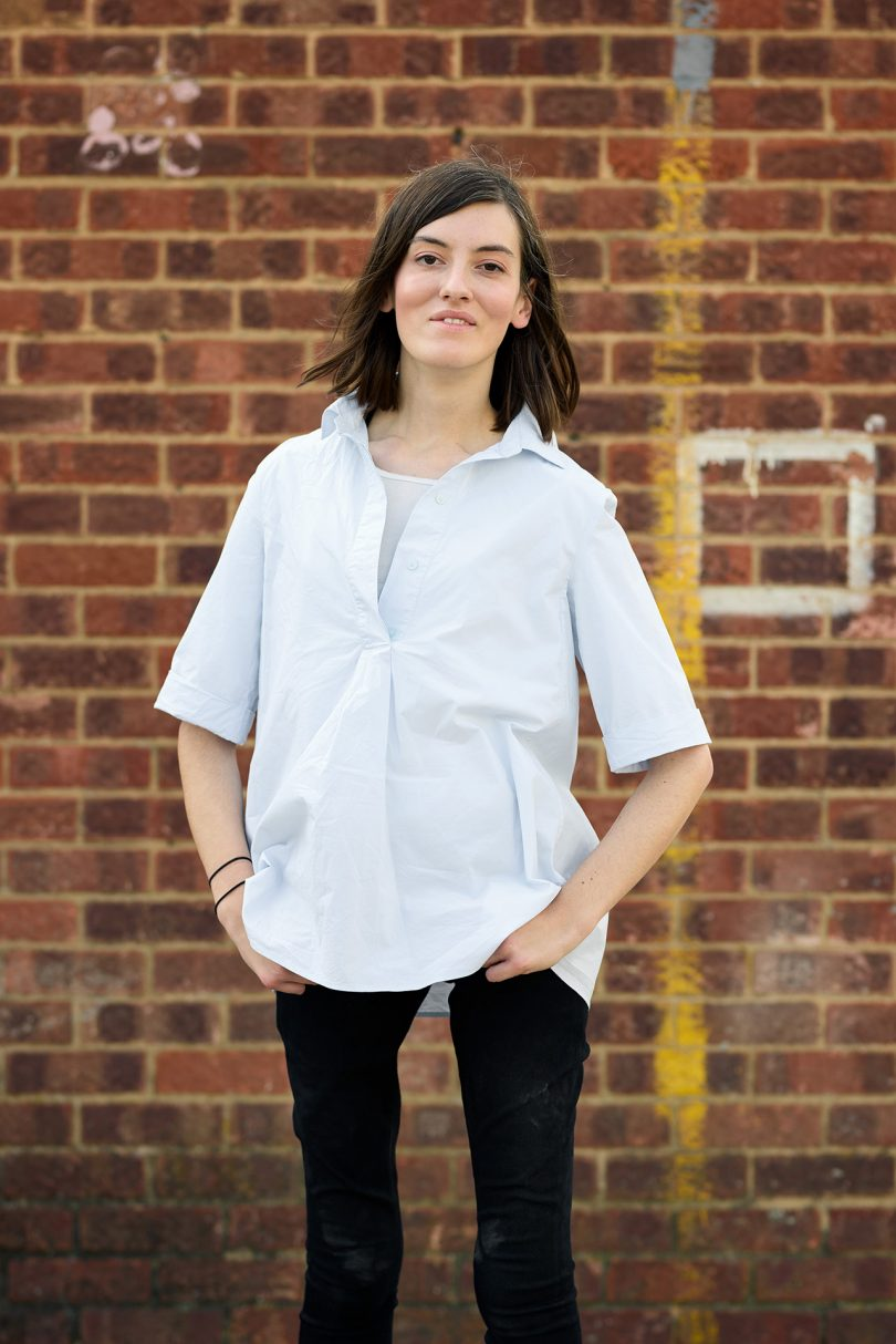 light skinned woman with dark hair wearing white short sleeved shirt and black pants
