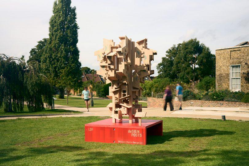 large street sculpture in American red oak on red pedestal