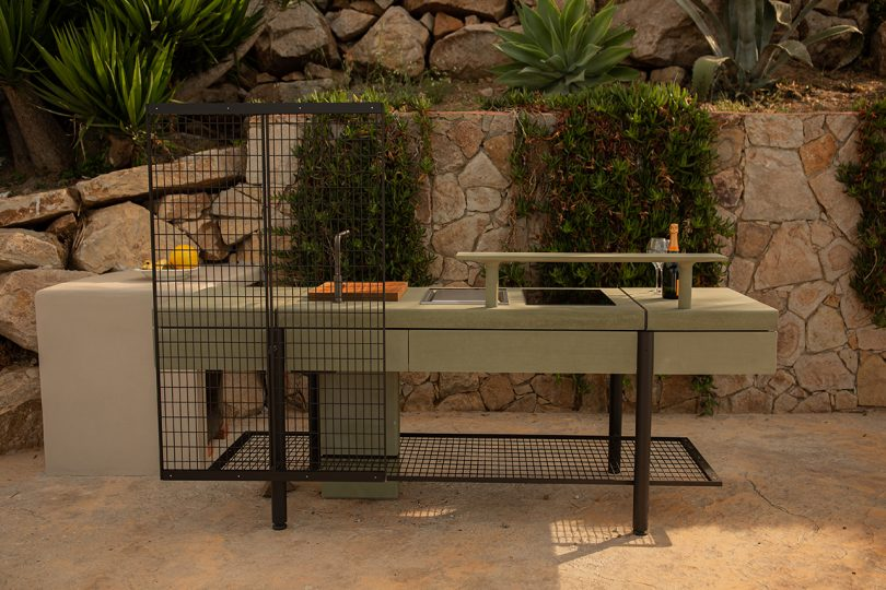 open space kitchen outdoors against rocky wall with vegetation
