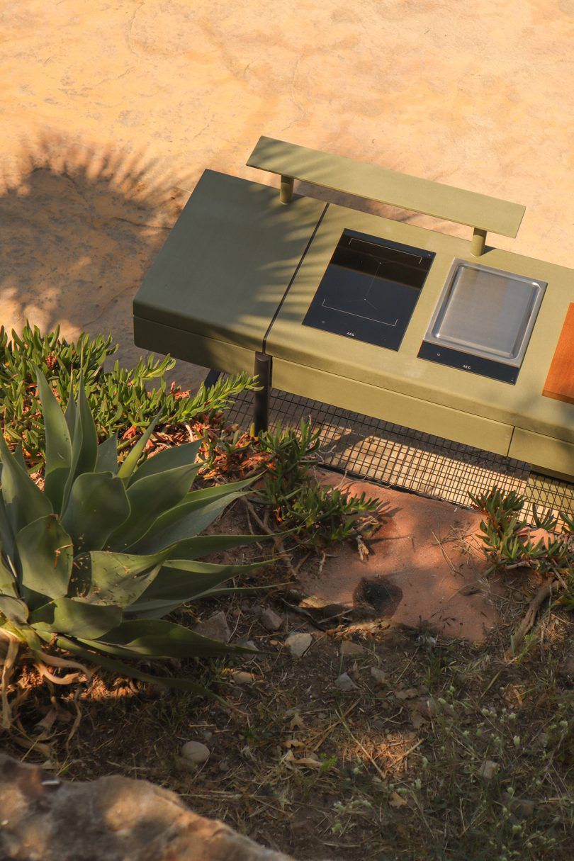 overhead shot of open space kitchen outdoors with vegetation