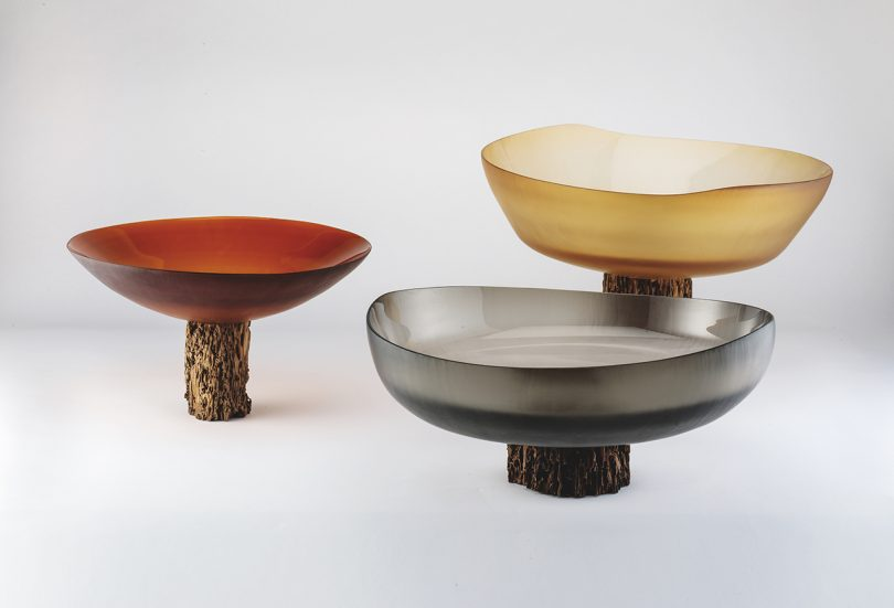 three bowls/vessels in muted hues on white background