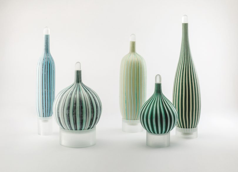 five striped murano glass vessels on a white background