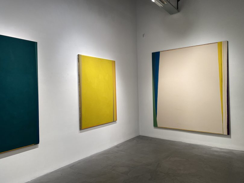 art gallery with white walls and three abstract paintings