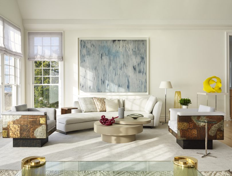 interior space in light colors with sofa, coffee table, and large artwork