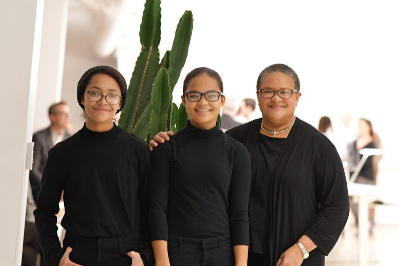 three brown skinned women wearing black with a cactus in the background