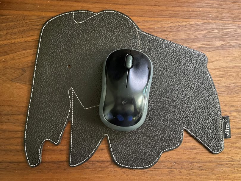 overhead photo of brown leather elephant mousepad sitting on a wood surface with computer mouse