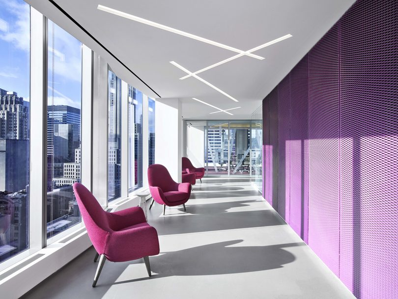 interior space wit lots of windows, three purple armchairs, and purple accent wall