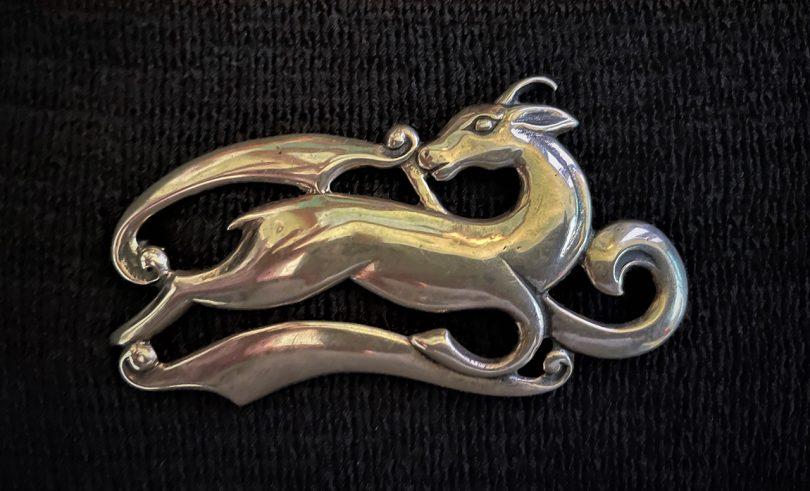 silver deer brooch on black background