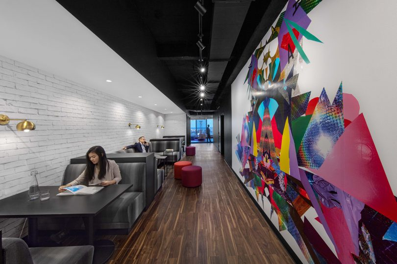 long and narrow interior space with booths on the left and a large colorful mural on the right wall