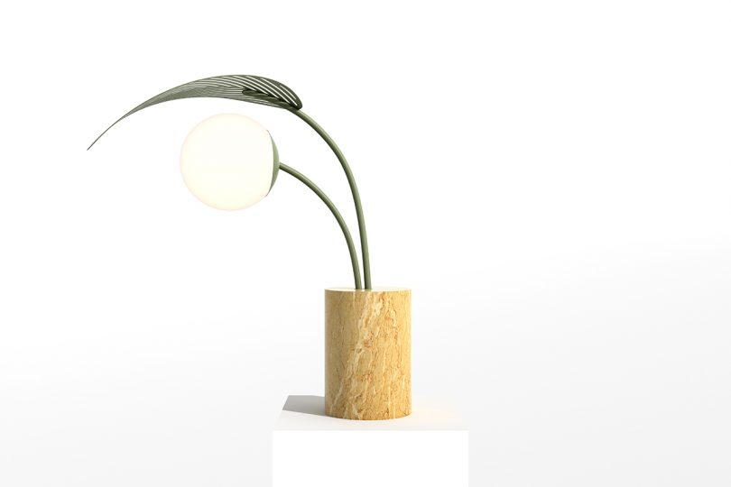 abstract modern table lamp resembling a palm tree on a white pedestal and white background