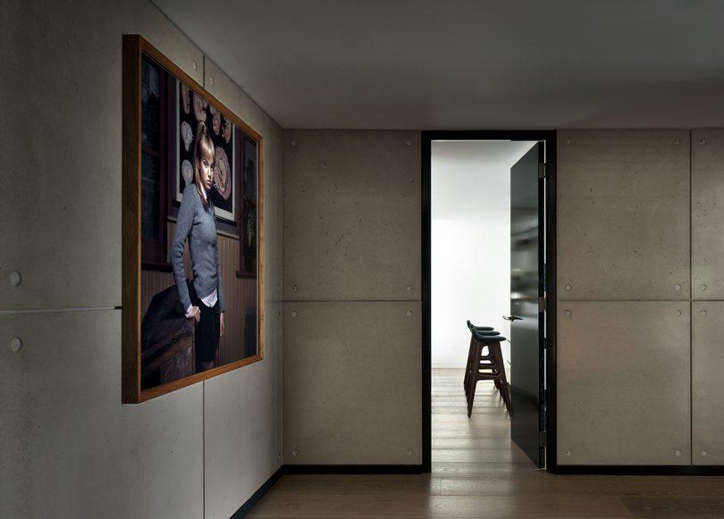 dark hallway with illuminated doorway and art on the left wall