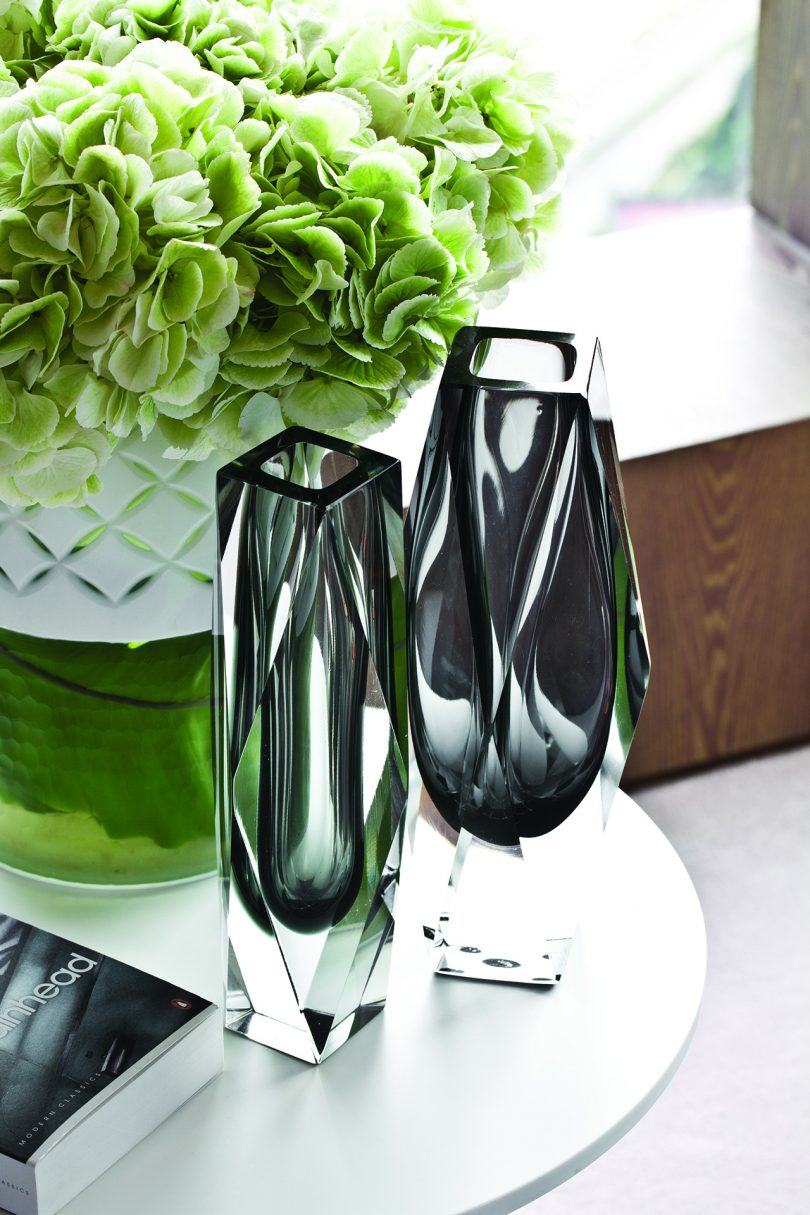 two empty glass vases next to one another with flowers behind them