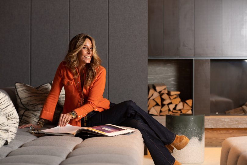 light skinned woman with light hair wearing orange blouse and black pants while reclining with a magazine in front of a fireplace