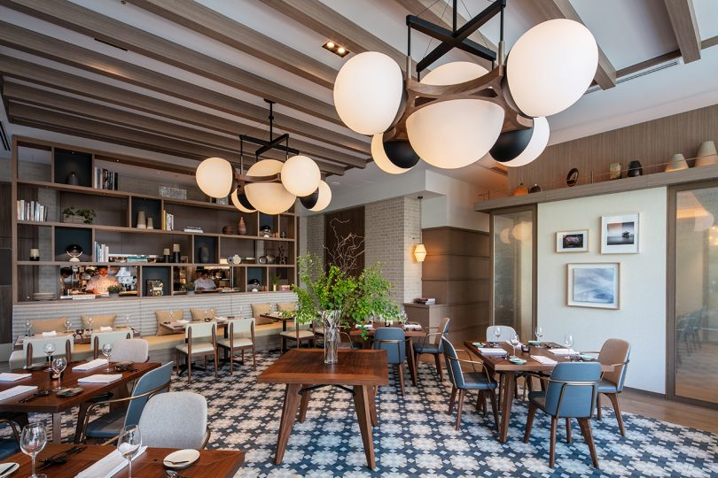 large eating space with booths, tables, statement lighting, and patterned floors