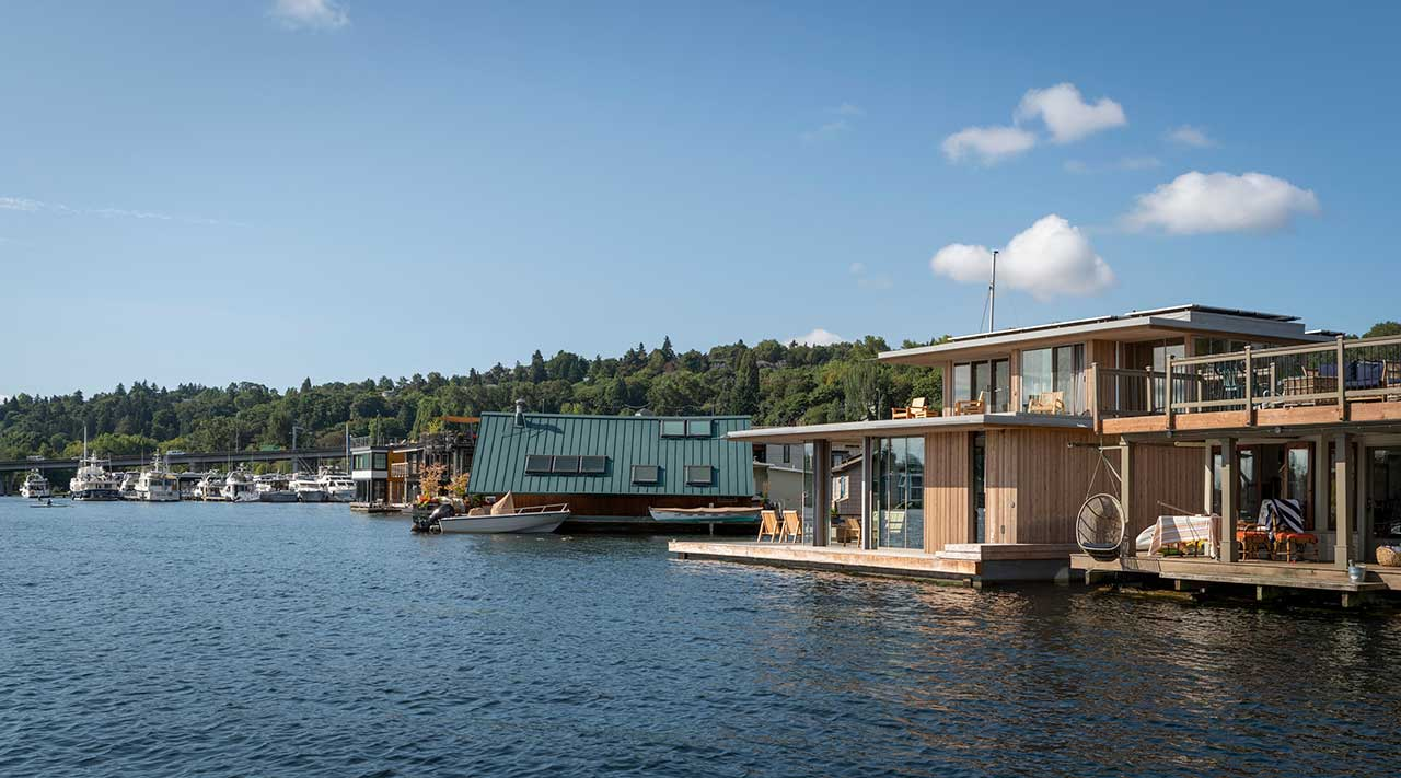 modern cabin floating in the water with houses behind on a hill