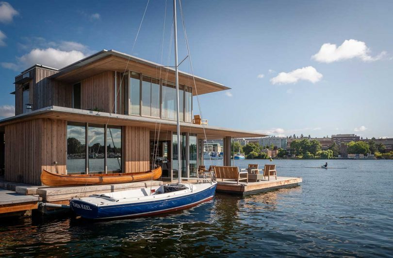 modern cabin floating in the water with docked sailboat
