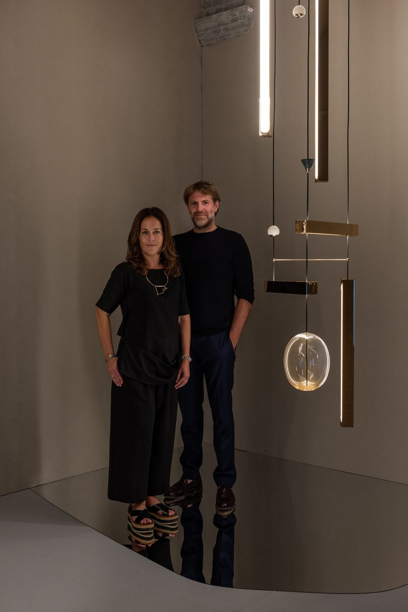 two lighted skinned people wearing black clothes posing with a light fixture in a dark space