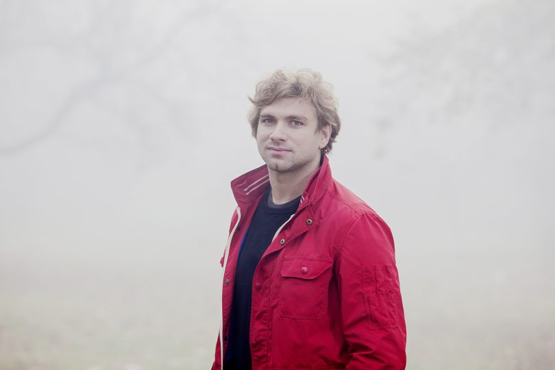 portrait of light skinned man with blonde hair wearing a black shirt and red jacket