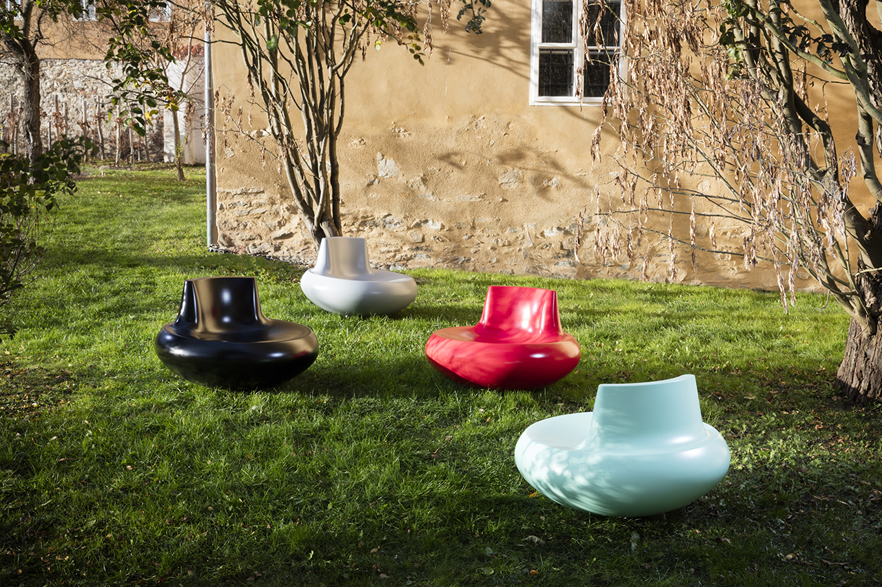 black, white, red, and light blue rounded chairs scattered around a grassy space