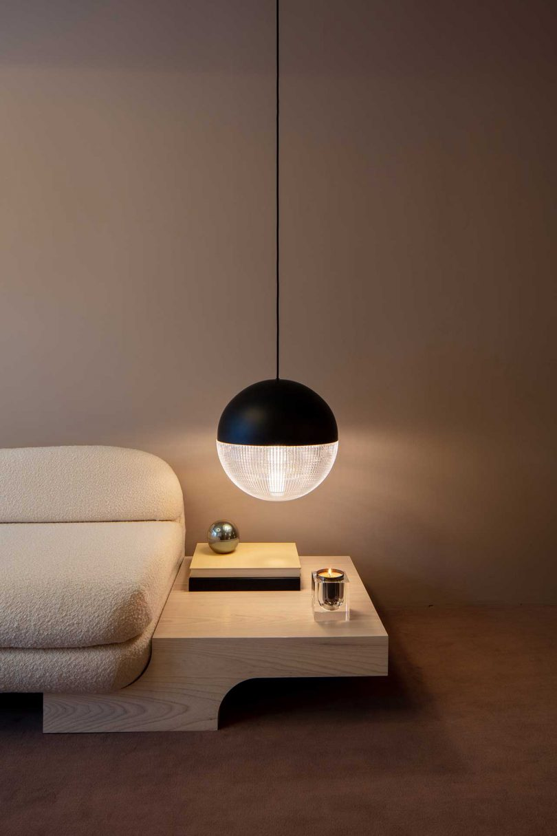 section of modern white sofa with built-in end table and suspended black and globe light fixture above