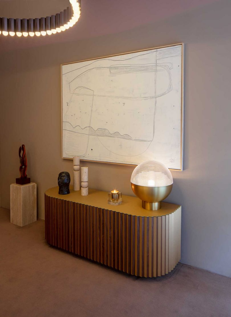 modern console with modern accessories and monochromatic painting above
