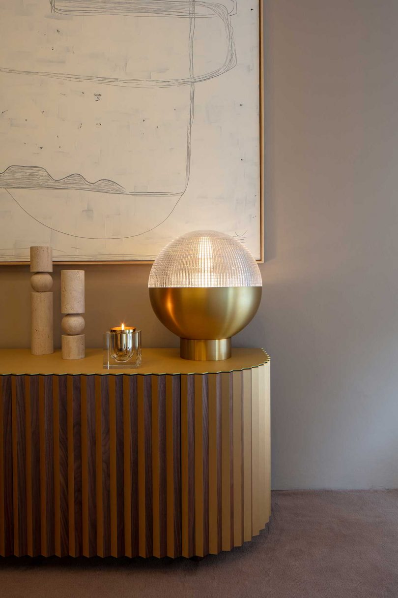 cropped view of a brass and glass globe lamp on modern console