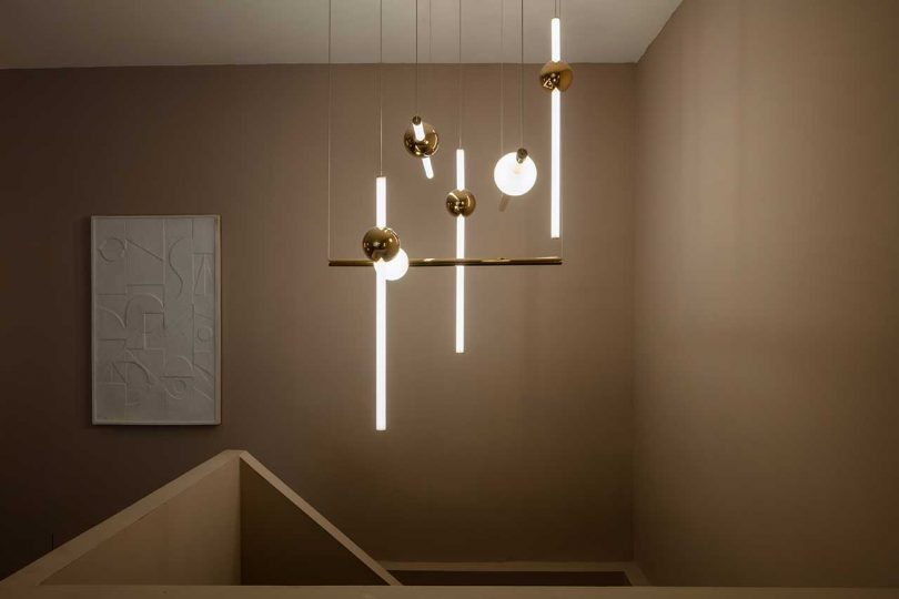 modern lighting fixture over stairs with lit rods and globes