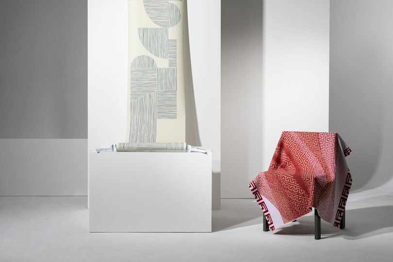ream of patterned wallpaper hanging and red textile draped over armchair