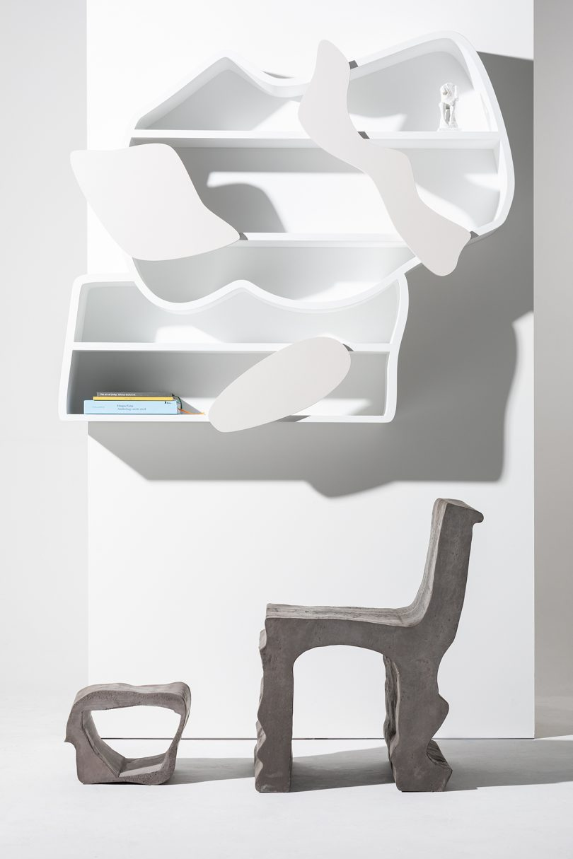 sculptural white wall shelf with organically shaped wood chair and stool