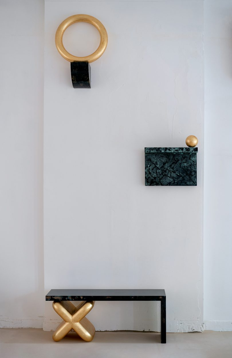 two patterned wall shelves and a bench with gold objects