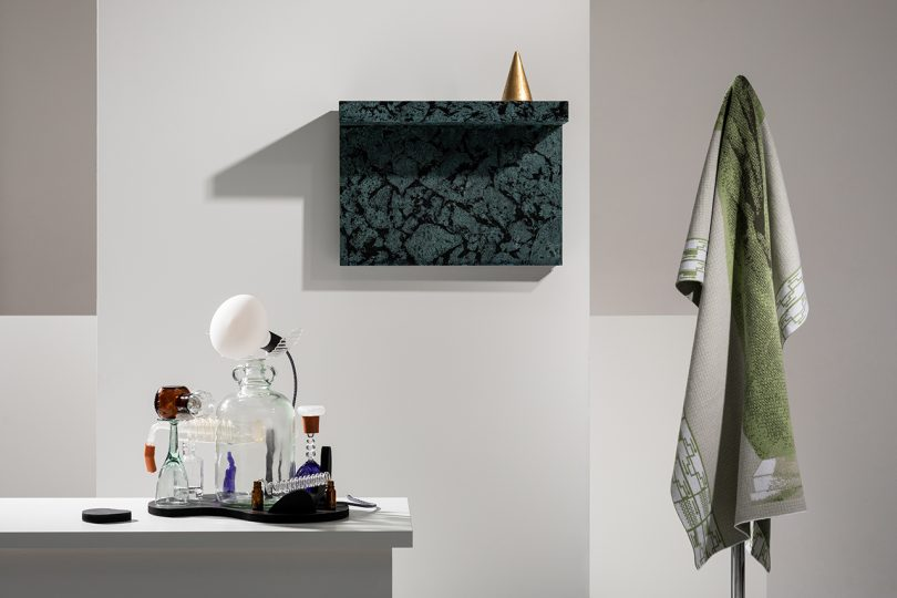 table with creative lamps, pattern wall shelf, and hanging grey textile