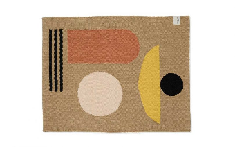 tan bath rug with earthy-colored shapes