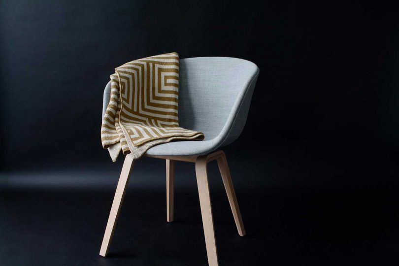 gold and beige maze patterned throw on a gray chair