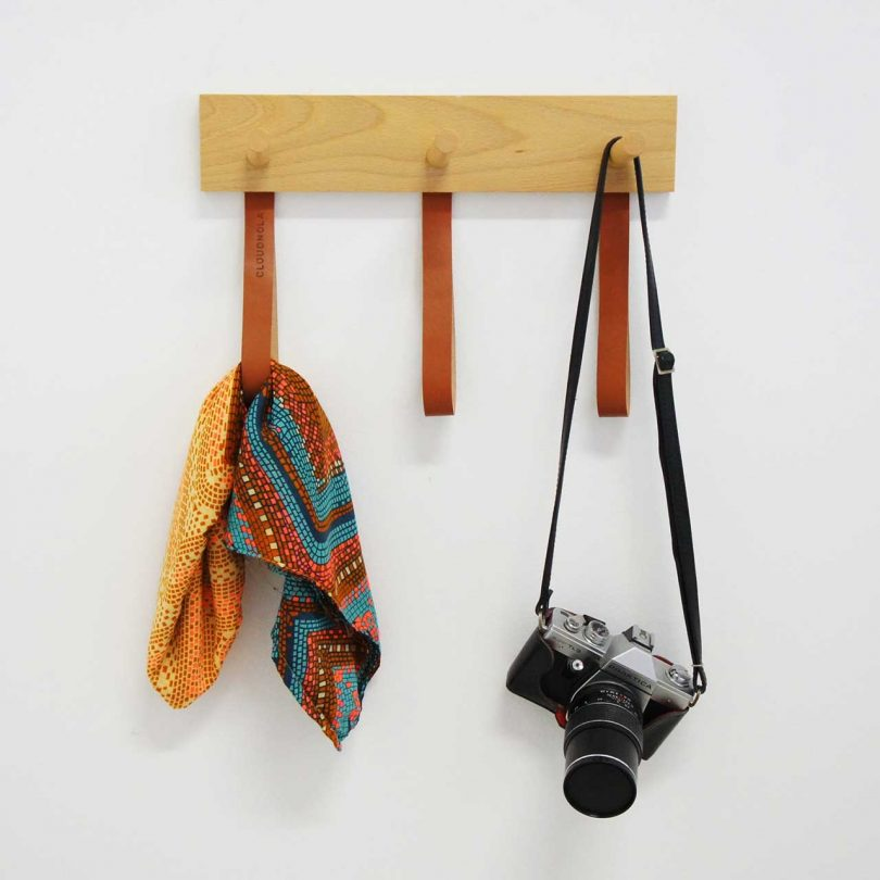 wall-mounted wooden coat rack with leather straps holding a scarf and camera