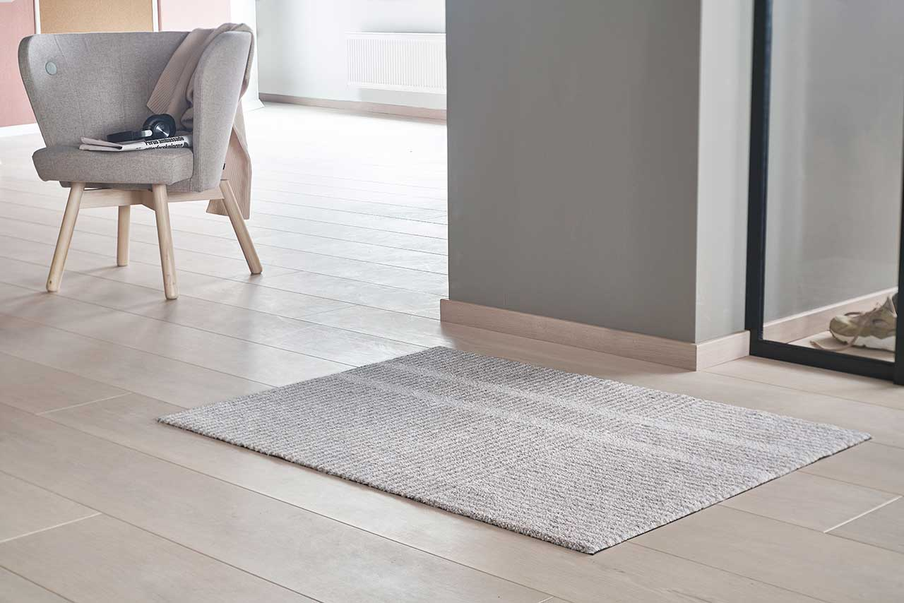 beige and white mat laying on pale wood floor with gray wall and window