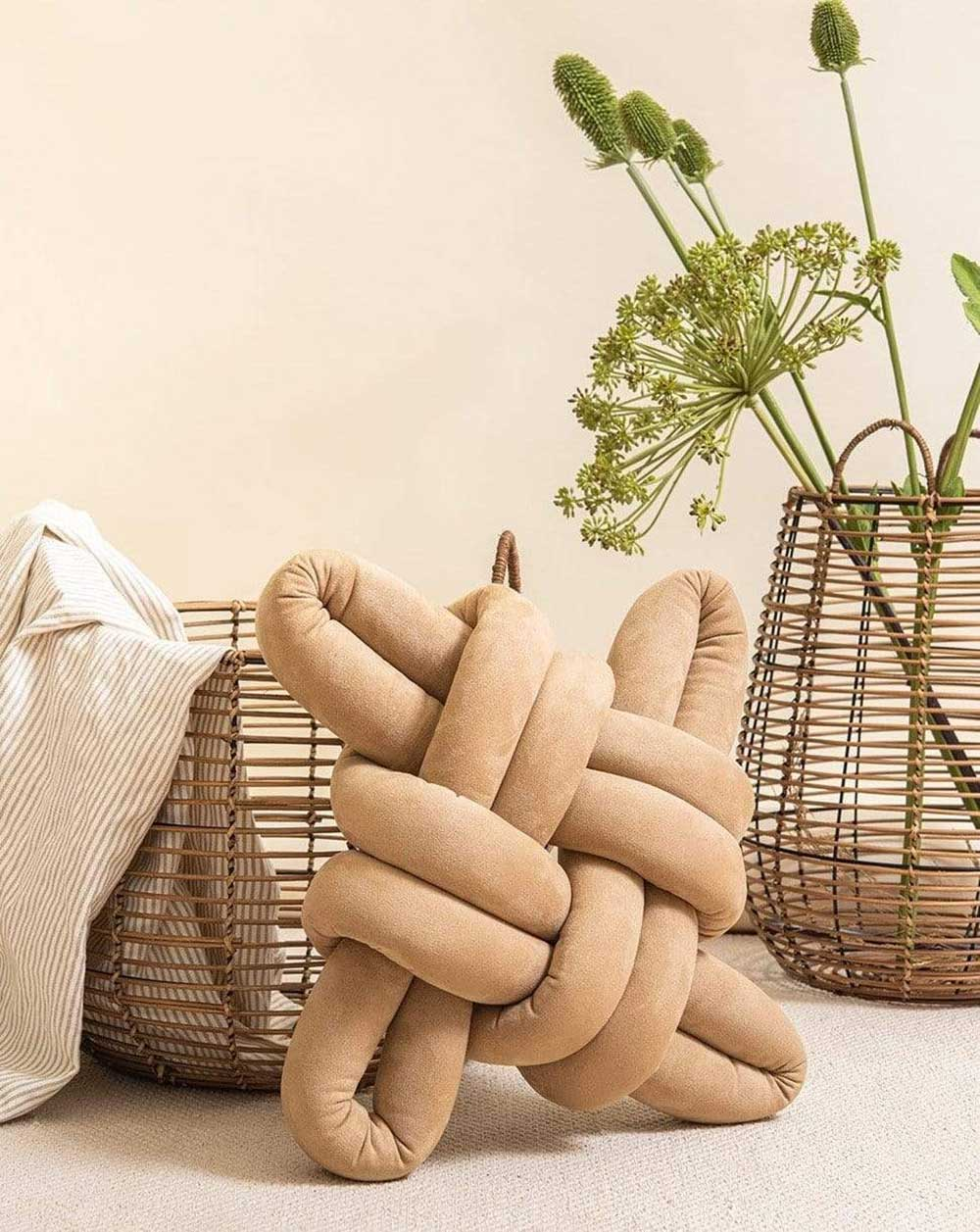 beige knot pillow resting in front of two baskets