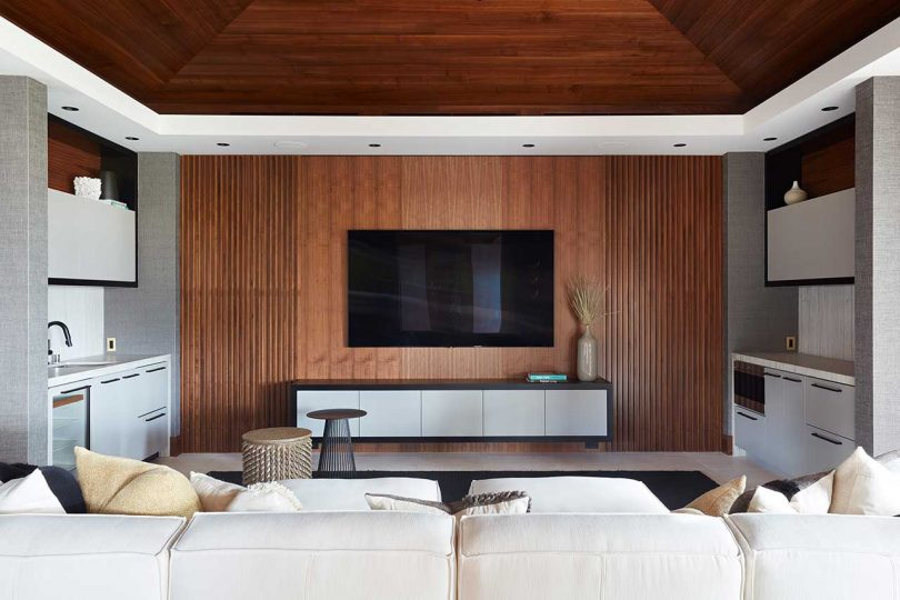 modern lounge area with white sofa facing tv hung on wall