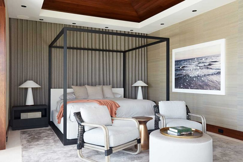 modern bedroom with black canopy bed and white linens with white chairs in a seating area