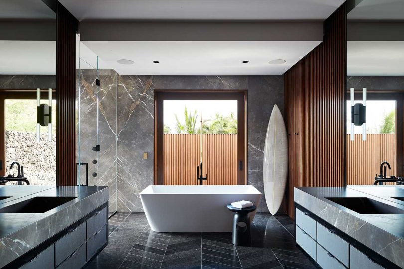 large modern bathroom with floating vanities on either side and a standalone white bathtub in front of a window
