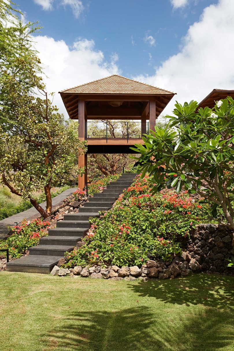 tropical yard with stairs leading to a covered pergola