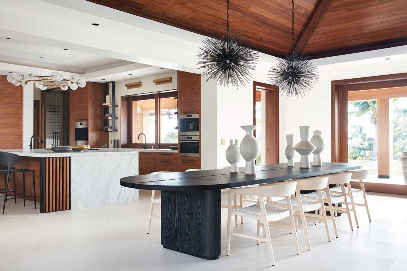 modern dining room with black table in front of kitchen