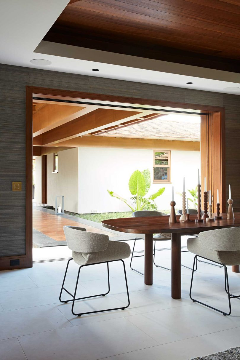 modern dining area opened up to the covered deck outdoors